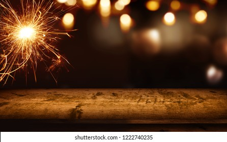 Background with sparkler and festive golden bokeh in front of empty rustic wooden table for a christmas decoration