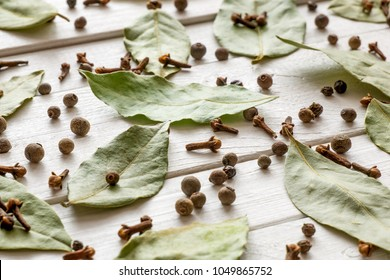Background of spices and condiments. Dried bay leaf, black pepper, cloves on a white wooden background. green laurel leaves on white table. Flat lay, top view