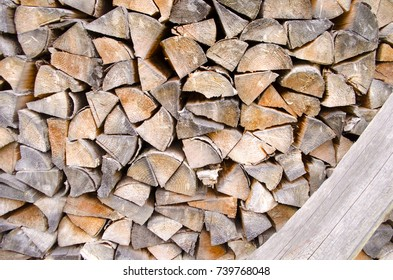 Background of splitted, dried and stacked firewood. Bunch of wood.