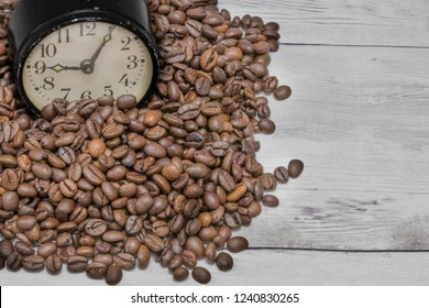 Background sprinkled with coffee beans with retro clocks
