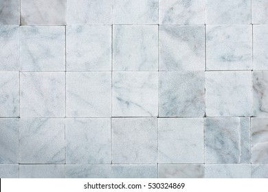 Background with square tiles of white Carrara marble. Tuscany, Italy