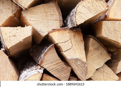 Background from stack of firewood from birch tree, for heating house, stacked in backyard, uncut wood, birch. Concept eco-friendly home heating during cold season. Soft selective focus. Horizontal.