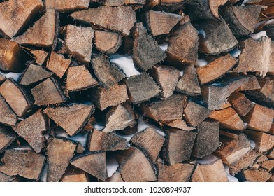 Background stack of firewood with snow