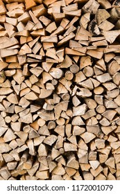 Background of stacked, dry chopped logs used for firewood.