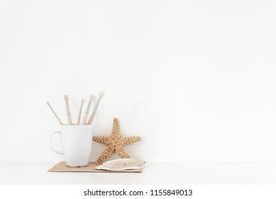 Background with stationary, seashells, sea star, mug, painting brusheson on white wall background, stylish home decor. Copy space for text. Good buy summer. Empty space for lettering.