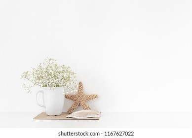 Background with stationary, seashells, sea star, bouquet of white flowers in mug on white wall background, cute soft home decor. Copy space for text. Empty space for lettering. Good buy summer
