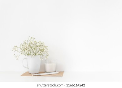 Background with stationary, white candle and bouquet of white flowers in mug on white wall background, elegant soft home decor. Copy space for text. Empty space for lettering, text.
