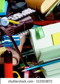 Background of Stationery Items with Notepads, Pens, Pencils, Paper Clips, Tape Dispenser, Sharpener, Stickers, Loop and Markers closeup