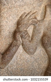 Background of stone statue showing a hand grasping the arm of another person