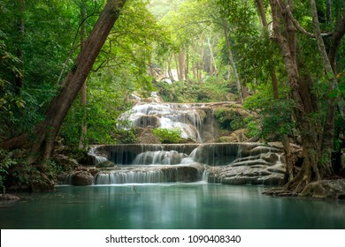 Background of streaming waterfall. This is Erawan waterfall in thai national park in deep forest on mountain. Around of brook has green jungle from big tree.The forest protected by forester all time.
