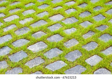 background of street stones between grass