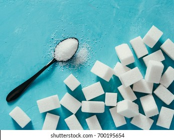background of sugar cubes and sugar in spoon. White sugar on blue background. Sugar with copy space. Top view or flat lay