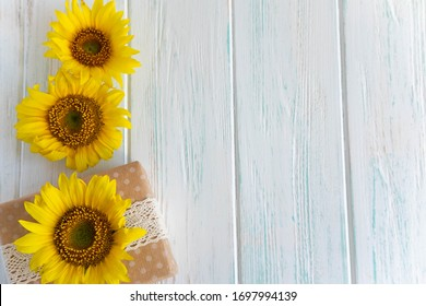Background with sunflower flowers on a white wooden background with a gift box. Design for a greeting card with flowers.