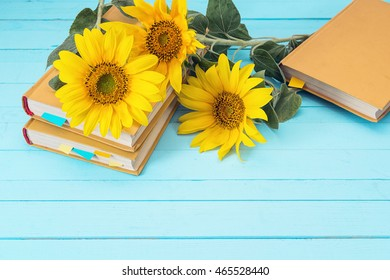 Background with sunflowers and yellow book on blue wooden boards. Space for text.