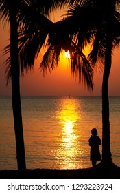 Background sunset on the beach. Silhouette of a girl standing at the sea under a coconut tree. The beach at Bang Darn, Chonburi, on 23 January 2019.