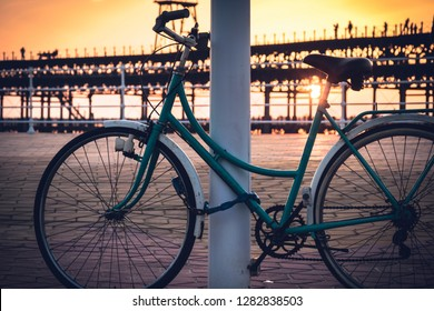 With the background of a sunset on the Rio Tinto dock, a vintage bicycle remains tied to a pole in Huelva, Andalusia, Spain