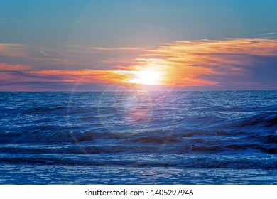 Background with sunset on the sea landscape: Sand beach with endless horizon and incredible foamy waves under the bright sundown with intense orange and red colors and clouds above the sea
