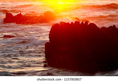 Background of Sunset over Ocean with Silhouetted Rocks and Copy Space