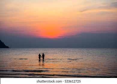 The Background of the sunset with a silhouette couple holding their hand standing in the sea face against to the sunset.