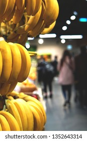 Background of supermaket with bananas in the foreground. Blurred image of customers choosing fruits.