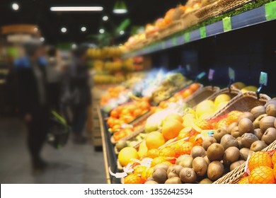 Background of supermaket with different fruits. Blurred image of customers choosing fruits.