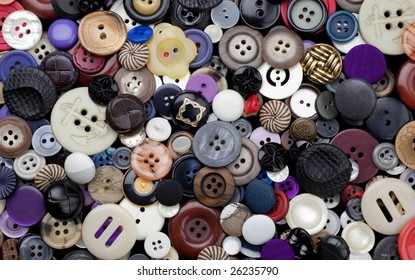 Background surface filled with a variety of dress-maker and clothing buttons, many of them vintage.