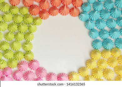 Background from sweet colored meringue. View from above. Colors of rainbow. Awesome sweet food on white background
