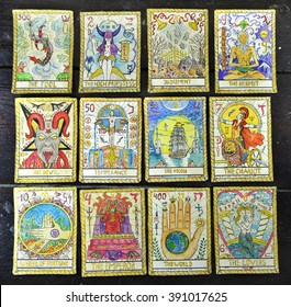 Background with the tarot cards, top view. The major arcana deck. Fortune telling seance or black magic ritual. Scary still life with occult and esoteric symbols. Halloween or divination rite