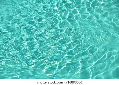 Background of teal blue water of pool with waves and ripples on surface, high angle view