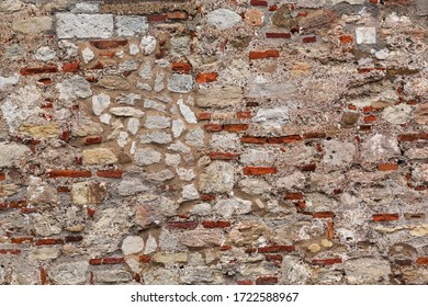 Background texture of an ancient stone wall on a medieval fortress with irregular pattern of rough stone interspersed with red clay brick and lime mortar