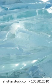 Background and texture of blue transparent ice sheet in stacked and reflect the sunlight (soft focus).