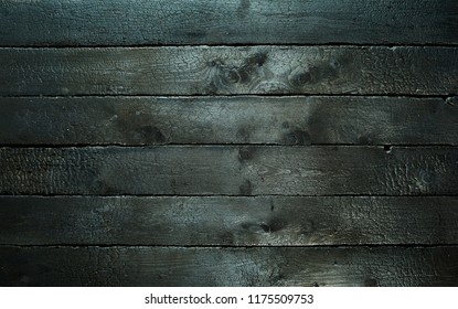 Background texture of burnt scorched wood blackened by a fire in a full frame view for barbecue themes