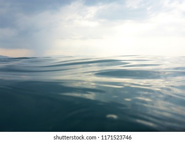 Background texture of clear, blue sea seen from water level and a cloudy evening sky