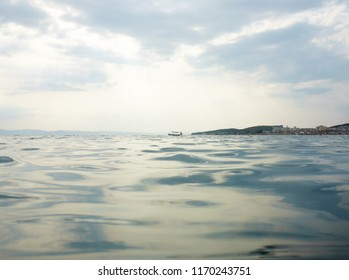 Background texture of clear, blue water and a cloudy evening sky with a small boat in the background.