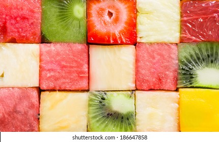 Background texture of diced tropical summer fruit cut in cubes and arranged in rows for a seamless pattern with watermelon, strawberry, kiwifruit, pineapple and melon