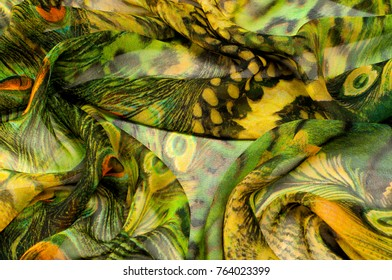 Background texture, drawing. Silk fabric. Light airy fabric. Green with peacock feathers. Yellow shade. Fabric cotton silk batiste mint green airy very light transparency