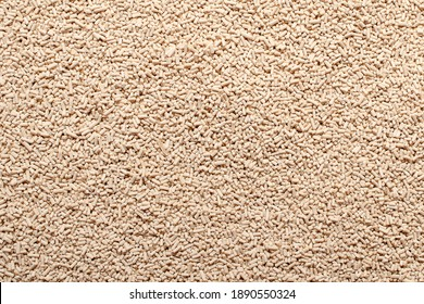 Background, texture from dry granular yeast, top view. Active dry yeast, top view. Heap of dry yeast granules, texture. Dry yeast is used in baked goods.
