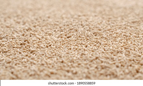 Background, texture from dry granular yeast, top view. Active dry yeast, top view. Heap of dry yeast granules, texture. Dry yeast is used in baked goods. Background for use on the label.