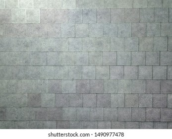 Background from texture of equal square rough gray plates. Decoration and design.