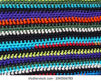 A background texture featuring multi colored strips of double crochet stitches.