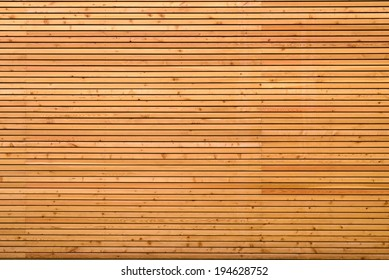 Background texture of finely slatted natural brown wood in a parallel pattern used in building decor and construction