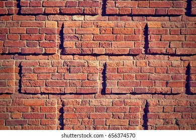 background and texture of a fragment of a brick wall closeup in the photo in retro style