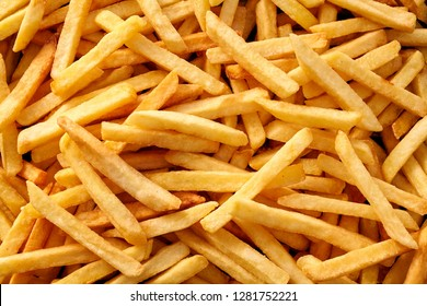Background texture of golden French fries or Pommes Frites sliced thin and viewed full frame from above