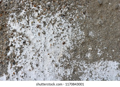 Background texture of a grey cement, stone wall with fading, distorted white paint.