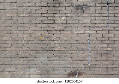 background texture of grungy brick wall at industrial building with cracks and moss