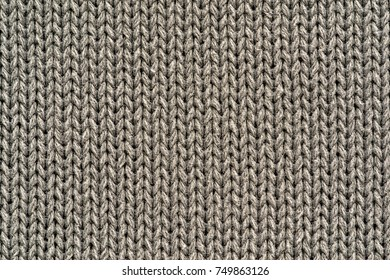 background and texture of knitted woolen or cotton fabric closeup beige color