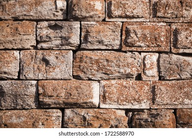 Background texture of a medieval stone wall on an ancient fortress showing the rectangular cut natural rock blocks or bricks of irregular sizes