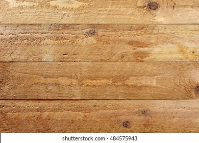 Background texture of natural rough wood planks with knots arranged parallel horizontally for product placement or as an architectural building concept