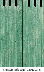 Background texture of old green painted weathered wooden planks forming an exterior cladding on a wall of a building or a fence