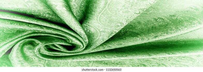 """Background texture, pattern. Paisley Silk green Jacquard is a complex woven glossy fabric with a woven design. Weaving creates the effect of a """"shadow"""" pattern or print."""